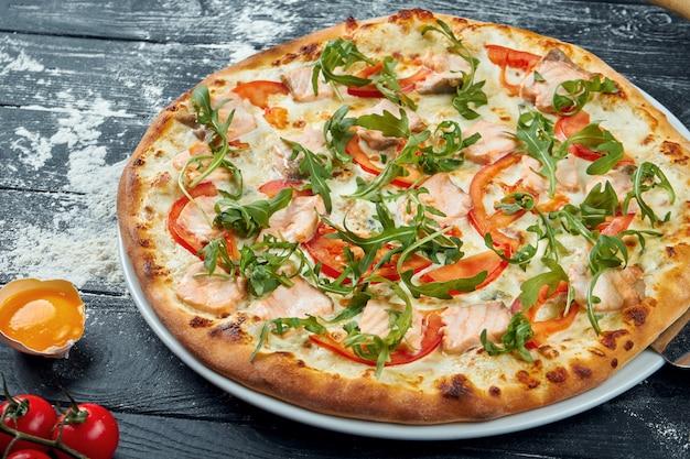 サーモン、トマト、溶けたチーズ、ホワイトソース、ルッコラ、成分の組成の黒い木製のテーブルで焼きたてのピザ。上面図。イタリア料理