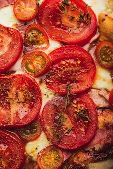 Baked pizza with whole grain dough, tomato, ham, mozzarella, tomato sauce, thyme.close up.