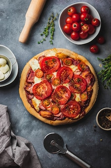Baked pizza with whole grain dough, tomato, ham, mozzarella, tomato sauce, thyme searved on gray stone wall with various ingredients for cooking, pizza knife and rolling pin. pizza preparation.