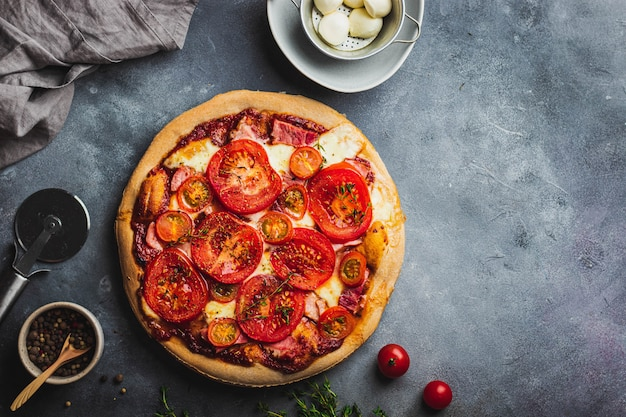 Baked pizza with whole grain dough, tomato, ham, mozzarella, tomato sauce, thyme served on gray stone background with various ingredients for cooking. pizza preparation.