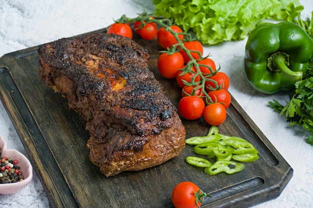 Baked pork chopped in a walnut and mint sauce on a cutting board with fresh herbs and vegetables.