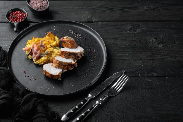 Baked pork fillet loin with potatoe and herbs set, on plate dish, on black wooden table