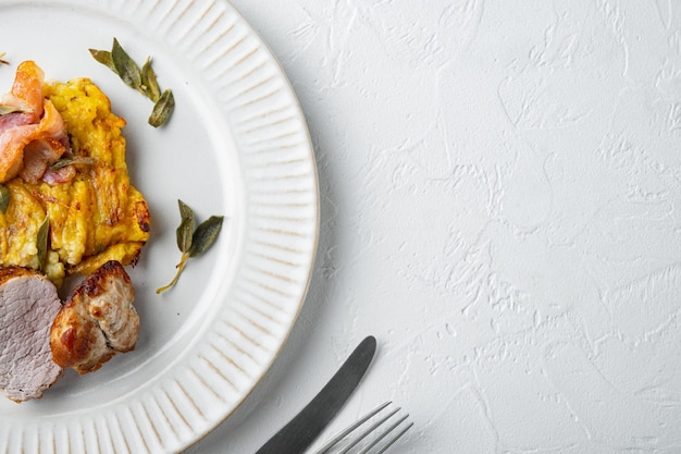 Baked pork fillet loin with potatoe and herbs set, on plate dish, on white stone