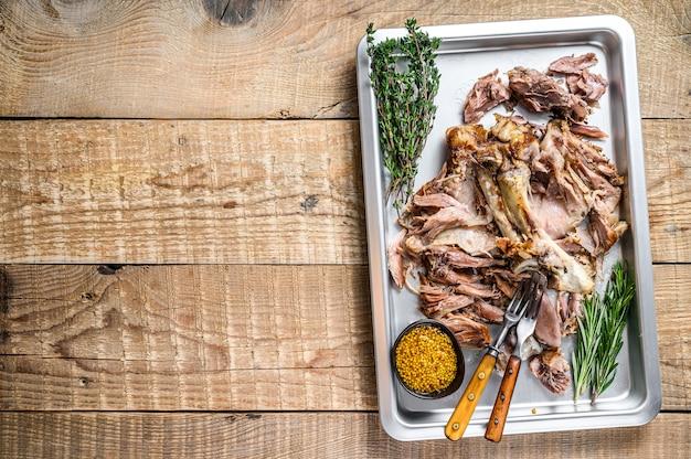 허브와 함께 베이킹 팬에 구운 돼지고기 너클 eisbein 고기. 나무 배경입니다. 평면도. 공간을 복사합니다.