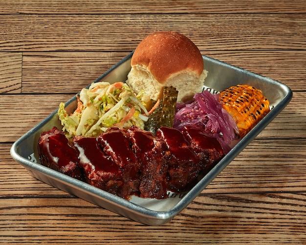 플라스틱 트레이에 바베큐 소스와 야채 장식을 곁들인 구운 돼지고기 허리