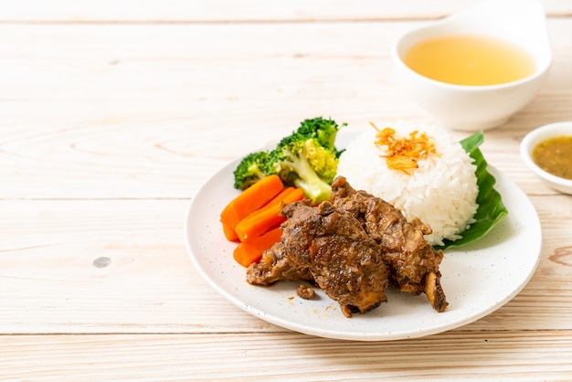 Baked pork ribs with sauce and rice Premium Photo