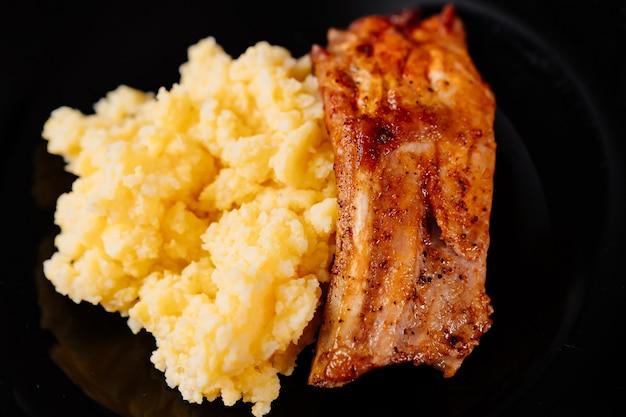 검은 배경에 반찬과 함께 구운 돼지 갈비. 음식의 일부. 집이나 식당에서 점심. 야외 파티