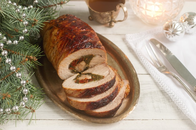 Baked pork roll stuffed with chard and sundried tomatoes served with sauce in christmas decorations.