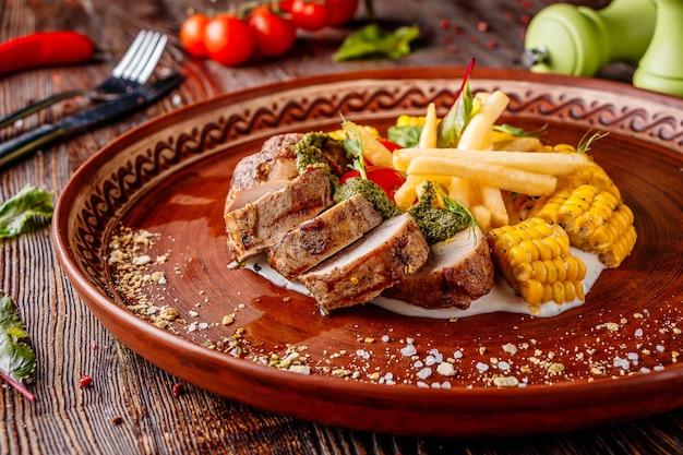 Запеченная свинина с картофелем фри, кукурузой и соусом песто, ресторанное блюдо, горизонтальная ориентация, крупным планом