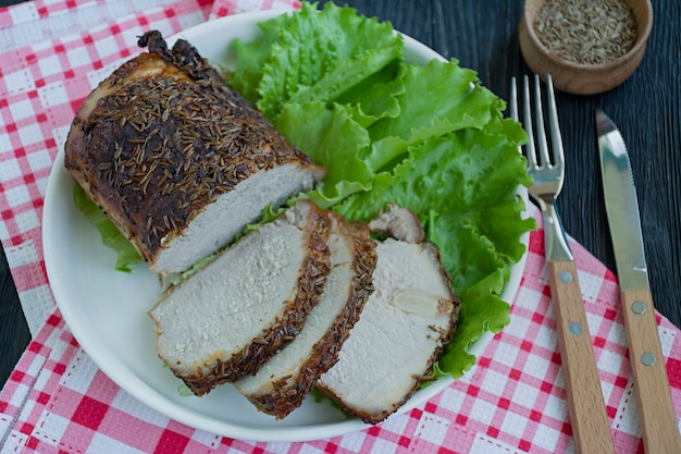 Baked pork tenderloin in spices sliced on a white plate with green salad.