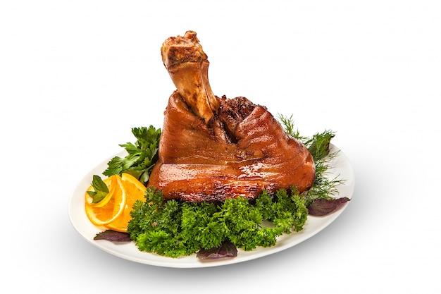 구운 돼지 고기, 전체 다리, 흰색 테이블에 싱싱한 식욕을 돋우는 크러스트가있는 거대한 부분. 외딴