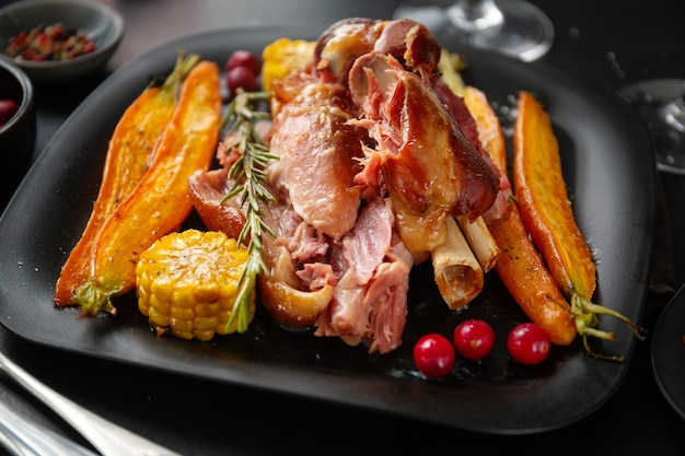 Baked pork with vegetables and spices on plate. closeup