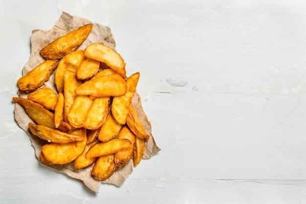 Ломтики запеченного картофеля на старой бумаге. на белом деревенском фоне.