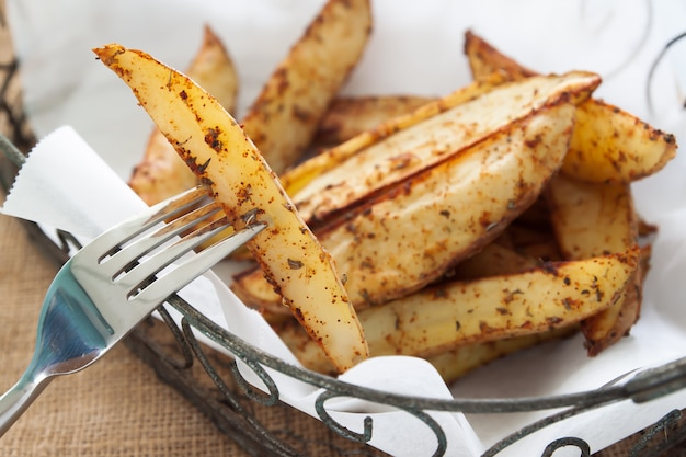 Baked potato wedges on basket - homemade organic vegetable, vegan potato wedges snack food meal