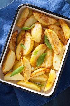 Baked potato wedges in enamel baking dish