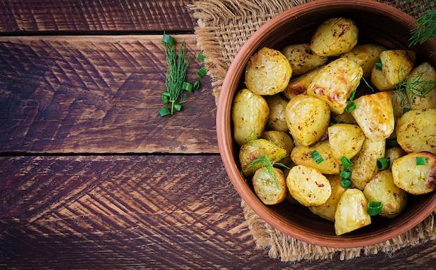 Запеченные картофельные дольки в миске на деревянном столе. вкусный обед. вид сверху, сверху