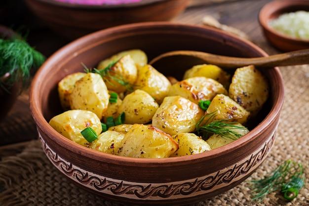Запеченные картофельные дольки в миске на деревянном столе. вкусный обед.