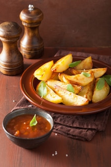 Baked potato wedges in plate over brown rustic table
