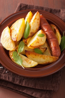 Baked potato wedges and sausage in plate over brown rustic table