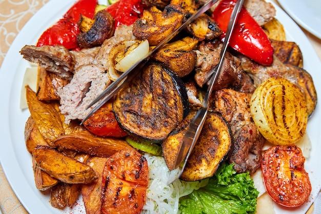 Запеченный картофель и овощи на гриле с шашлыком и сосисками. крупный план, выборочный фокус