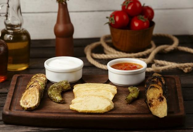 Patate al forno melanzane e zucchine su un tavolo di legno