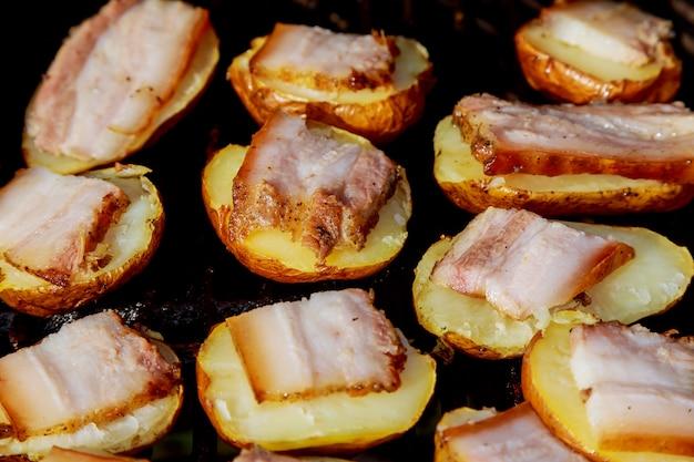 Baked potatoes grilled on skewers. street festival food.