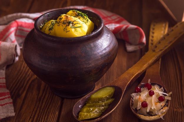 Запеченный картофель в старом горшке на деревянной поверхности с квашеной капустой и огурцом