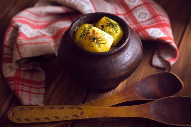 Запеченный картофель в старом горшке на деревянной поверхности