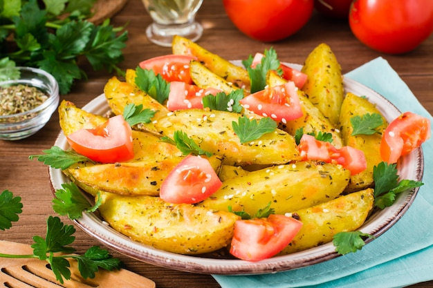 Baked potatoes in a peel with tomatoes in a plate, herbs and spices on a wood table