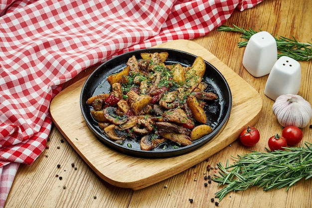 Baked potatoes smoked sausages, mushrooms in a pan on wood.