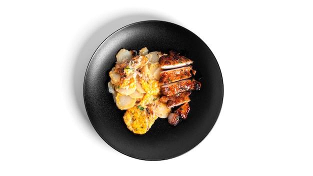 절연 검정 잉크 판에 치즈와 돼지 고기 스테이크와 구운 된 감자.