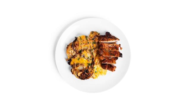 절연 흰 접시에 치즈와 돼지 고기 스테이크와 구운 된 감자.