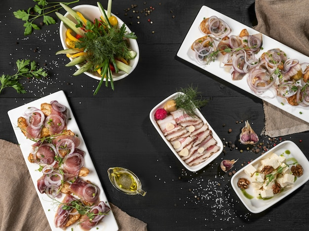 Запеченный картофель с рыбой, нарезанной свиной грудинкой, сыром и овощами на столе