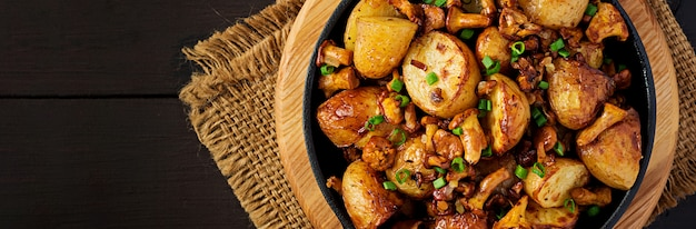 Baked potatoes with garlic, herbs and fried chanterelles in a cast iron skillet. top view