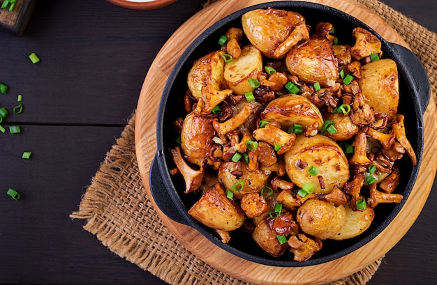 Baked potatoes with garlic, herbs and fried chanterelles in a cast iron skillet, top view