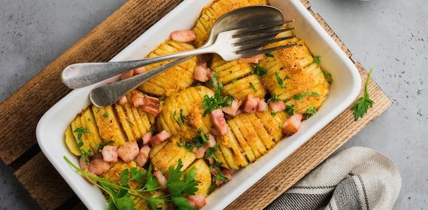 회색 밝은 배경에 햄, 허브, 빵 부스러기가 있는 구운 감자. 스칸디나비아 요리. 평면도. 프리미엄 사진