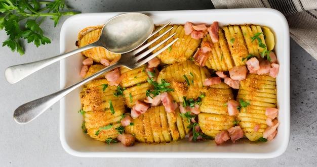 회색 밝은 배경에 햄, 허브, 빵 부스러기가 있는 구운 감자. 스칸디나비아 요리. 평면도.