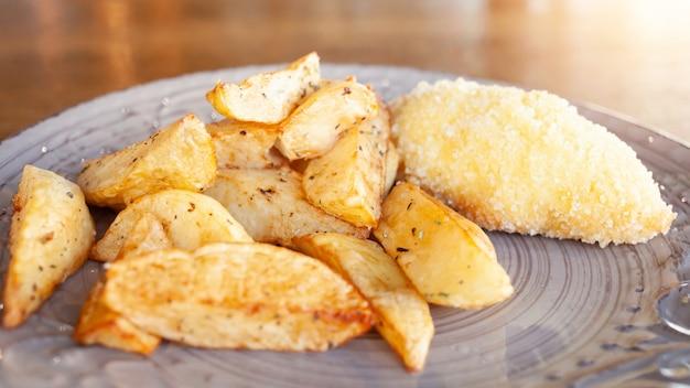 チーズとバターを使ったパン粉をまぶしたハーブとカツレツのベイクドポテト