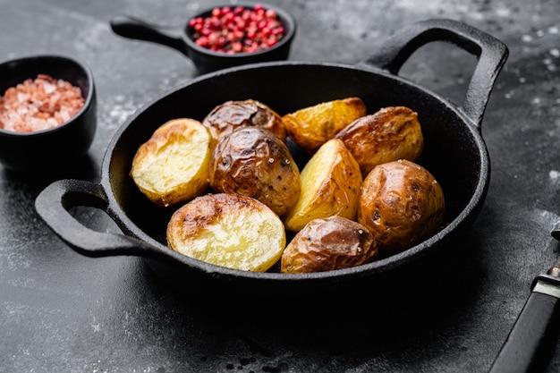검은색 돌 탁자 배경에 있는 프라이팬에 허브와 마늘을 넣은 구운 감자