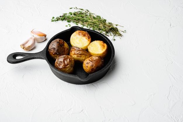 허브와 마늘 세트를 곁들인 구운 감자, 튀김 주철 팬, 흰색 돌 탁자 배경, 텍스트 복사 공간