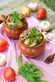土鍋にキノコと肉を入れたベイクドポテト。