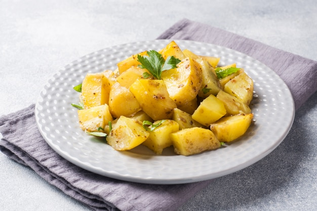 Baked potatoes with spices and herbs on a plate.