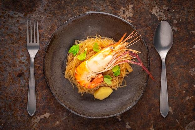Запеченные креветки с вермишелью, запеченные креветки со стеклянной лапшой в тарелке в стиле ваби-саби рядом с вилкой и ложкой на фоне ржавой текстуры, вид сверху, речная креветка