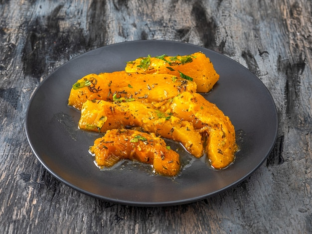Baked pumpkin slices with aromatic herbs on a black plate healthy food