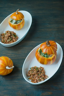 Baked pumpkins. small pumpkin stuffed with minced meat and sprinkled with cheese on top.