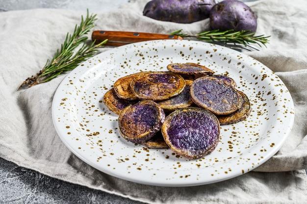 Запеченный фиолетовый картофель с розовой солью. серый фон вид сверху