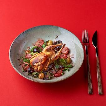 焼きウズラと新鮮な野菜を皿に盛り付けます
