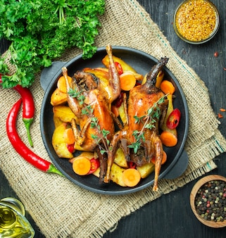 木製のテーブルの上の小さなフライパンで野菜とハーブと焼きウズラ。上からの眺め。閉じる。スペースをコピーします。