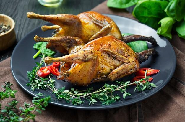 Запеченная перепела с овощами на тарелке. запеченная птица в духовке с овощами и зеленью на темном столе.