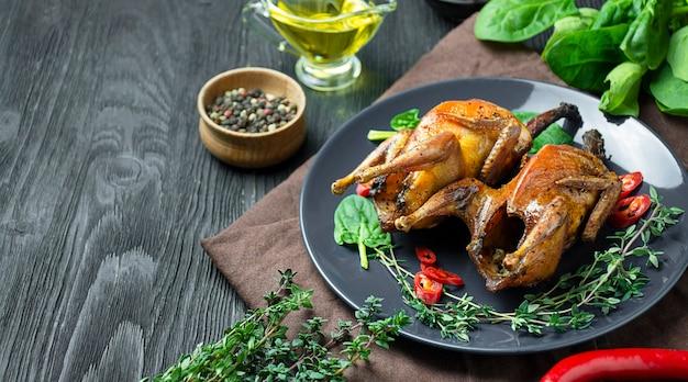 Запеченная перепела с овощами на тарелке. запеченная в духовке птица с овощами и зеленью. скопируйте пространство.